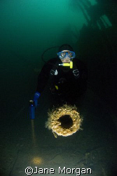 Diver inspects one of the 5 inch guns on the SMS Brummer.... by Jane Morgan 